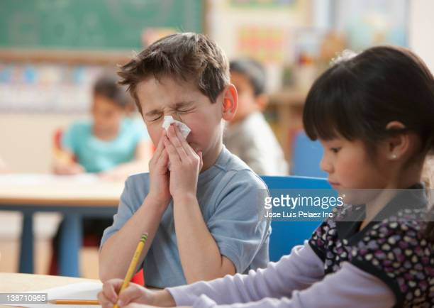 caucasian boy blowing nose in classroom - cold virus stock pictures, royalty-free photos & images