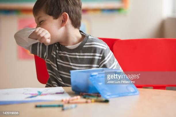 caucasian boy blowing nose in classroom - sonarse fotografías e imágenes de stock