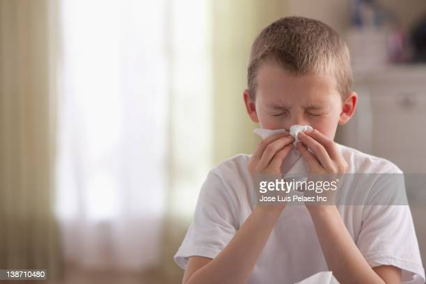 caucasian boy blowing nose - cold virus stock pictures, royalty-free photos & images