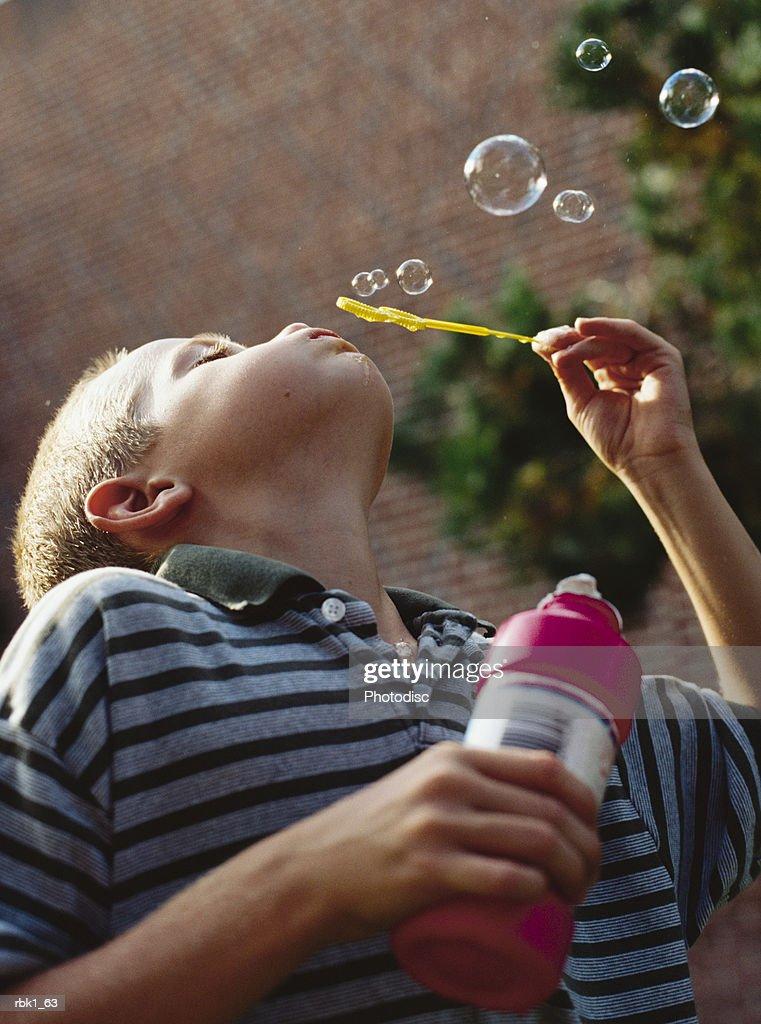 A caucasian boy blows bubbles outside : Stockfoto