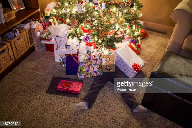 caucasian boy buried in christmas gifts - funny christmas stock-fotos und bilder
