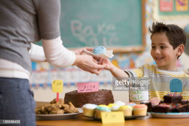 Caucasian boy buying cupcake at bake sale