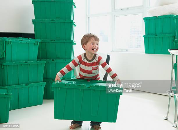 Caucasian boy carrying container in new home