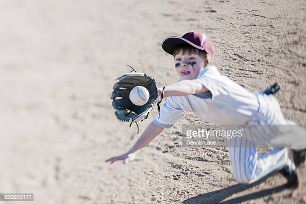 caucasian boy catching baseball on field - eye black stock photos and pictures