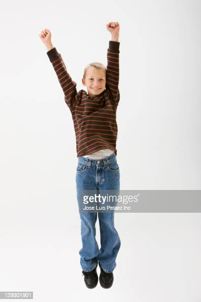 Caucasian boy cheering and jumping