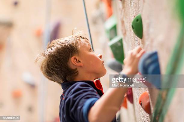 Caucasian boy climbing rock wall indoors