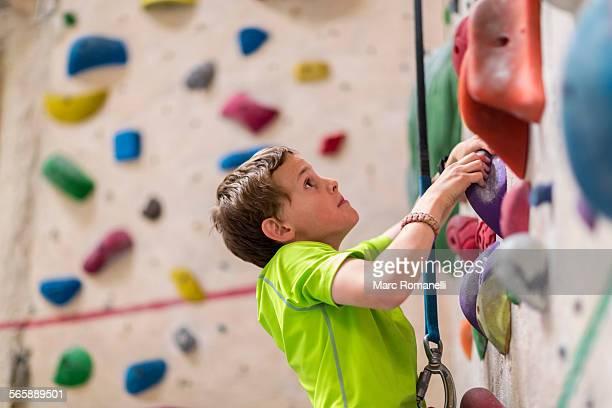 Caucasian boy climbing rock wall indoors