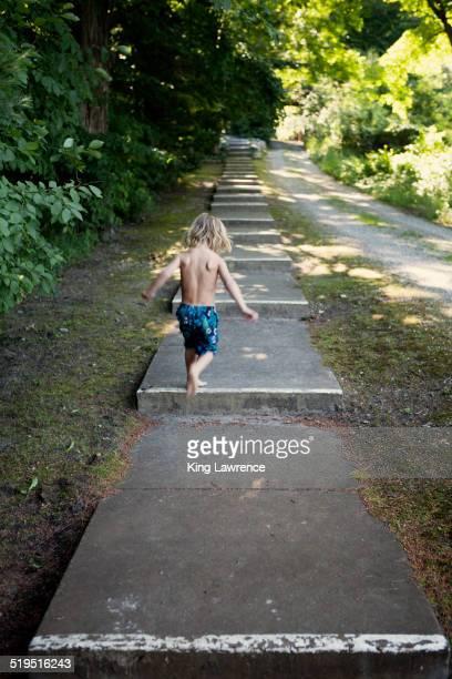 Caucasian boy climbing stairs near rural path