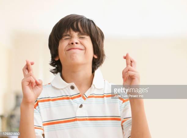 Caucasian boy crossing fingers