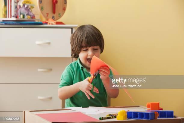 Caucasian boy cutting paper
