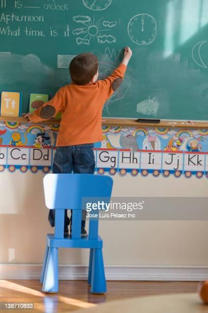 caucasian boy drawing on blackboard in classroom - solo un bambino maschio foto e immagini stock