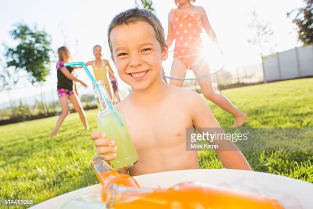 Caucasian boy drinking soda in backyard
