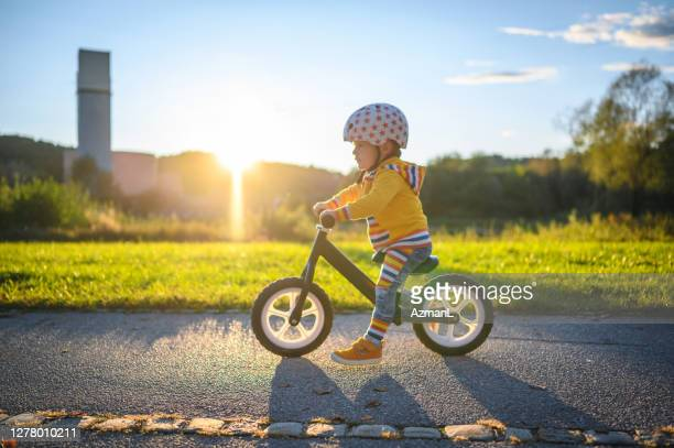 caucasian boy driving balance bike outdoors - balance stock pictures, royalty-free photos & images