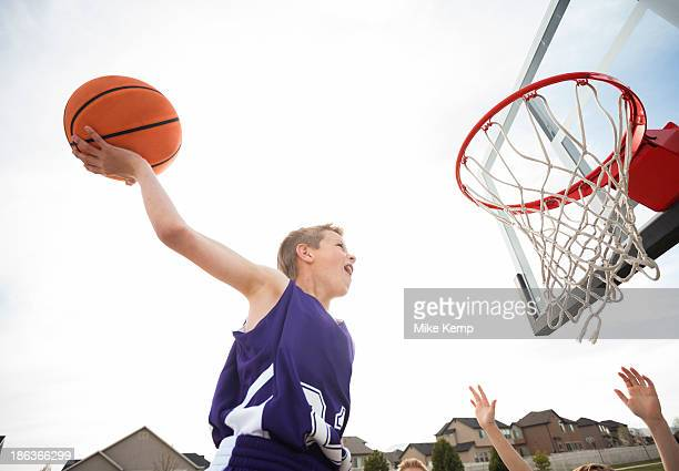 caucasian boy dunking basketball in hoop - making a basket scoring stock photos and pictures