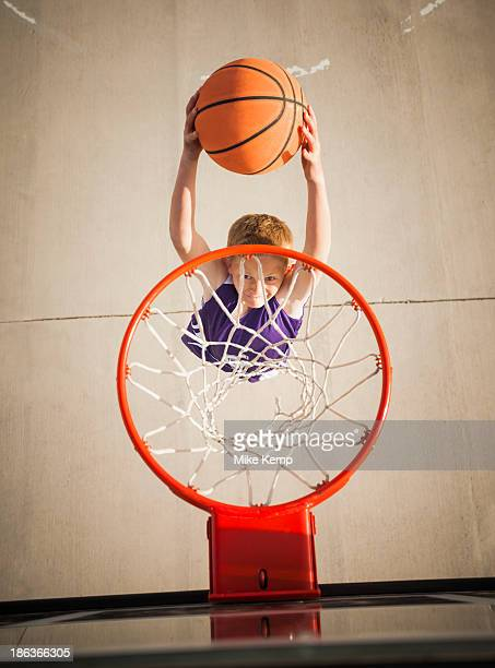 Caucasian boy dunking basketball in hoop