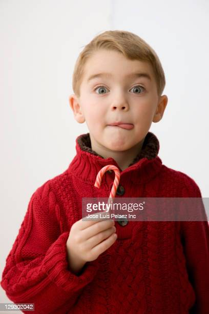 Caucasian boy eating Christmas candy cane