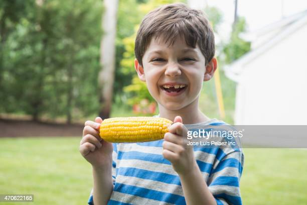 Caucasian boy eating corn on the cob