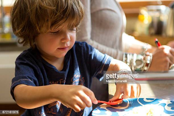 Caucasian boy eating food with plastic spoon
