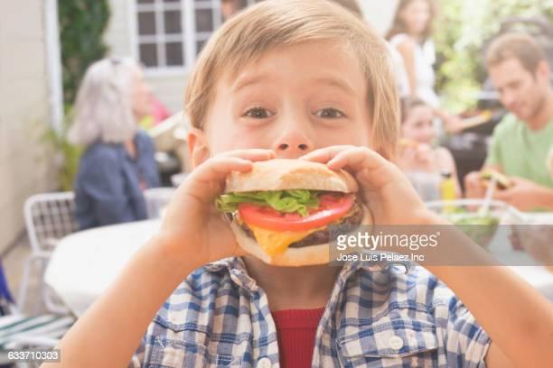 Caucasian boy eating hamburger at barbecue