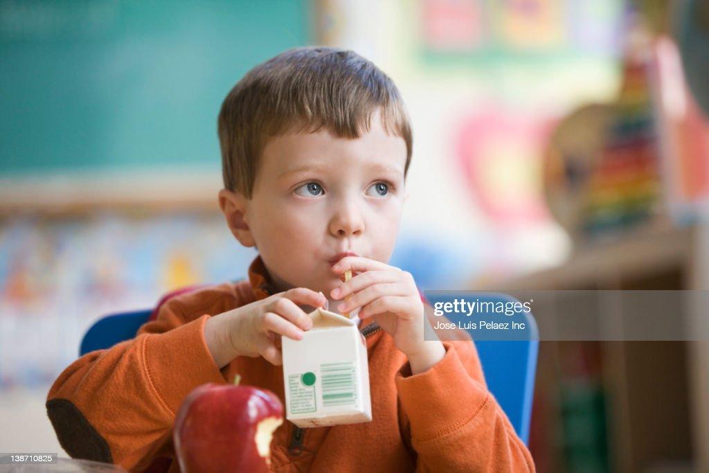 Caucasian boy eating lunch in classroom : Foto de stock