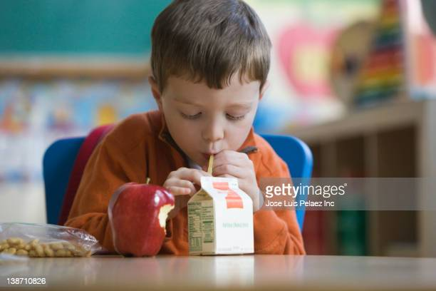 caucasian boy eating lunch in classroom - juice carton stock photos and pictures