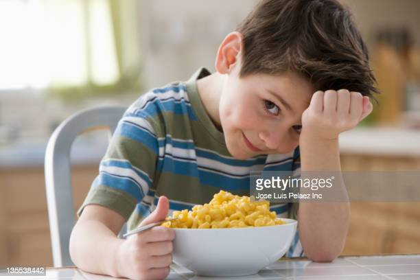 Caucasian boy eating macaroni and cheese