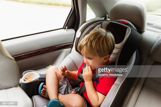 Caucasian boy eating snack in car seat