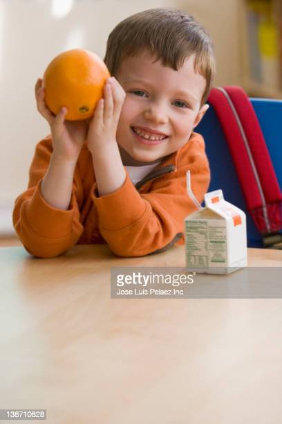 caucasian boy eating snack in classroom - juice carton stock photos and pictures