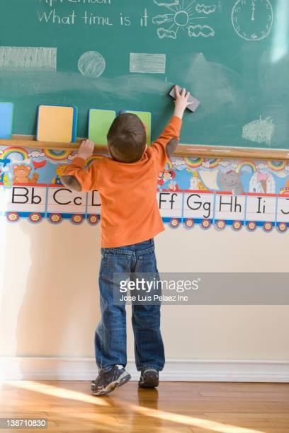 caucasian boy erasing blackboard in classroom - solo un bambino maschio foto e immagini stock