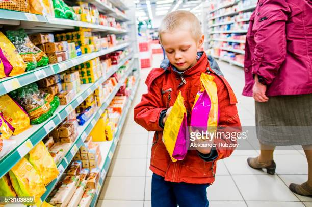 Caucasian boy examining bags of food in grocery store
