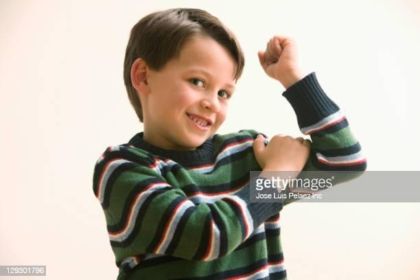Caucasian boy flexing biceps