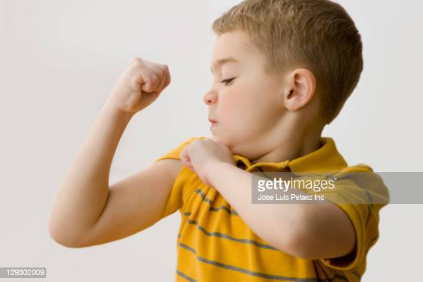 caucasian boy flexing biceps - human limb stock pictures, royalty-free photos & images