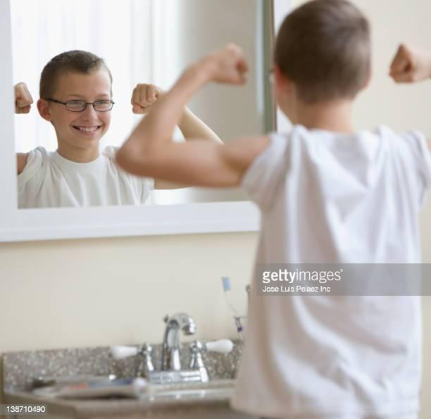 Caucasian boy flexing muscles in bathroom