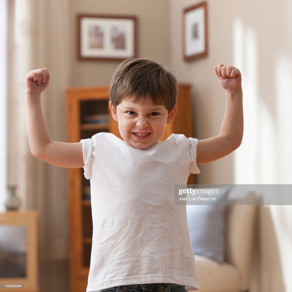 Caucasian boy flexing muscles : Stock Photo