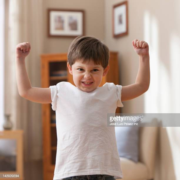 Caucasian boy flexing muscles