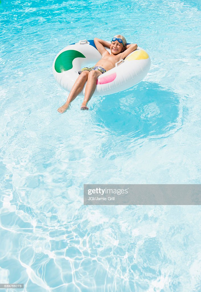 Caucasian boy floating in inflatable ring in swimming pool : Foto stock