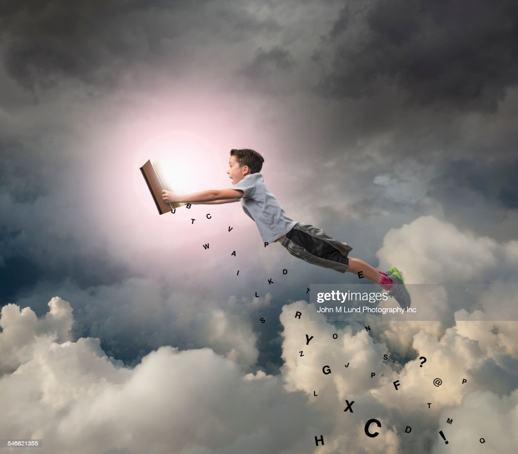 Caucasian boy flying with book in sky : Stock Photo