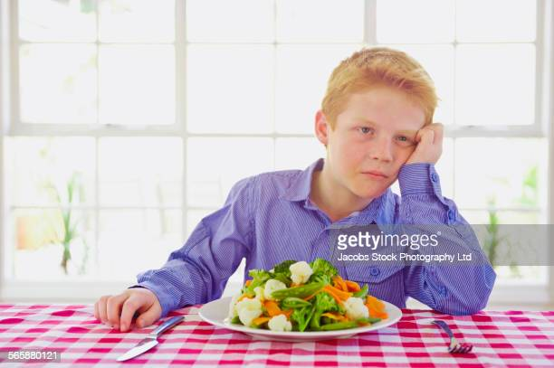 Caucasian boy frustrated with vegetables at table