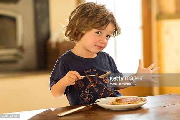 Caucasian boy gesturing while eating pancakes