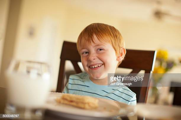 Caucasian boy giggling at dinner table