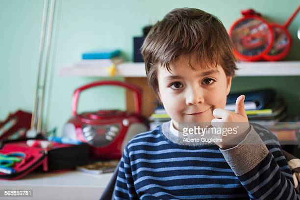 Caucasian boy giving thumbs up at desk