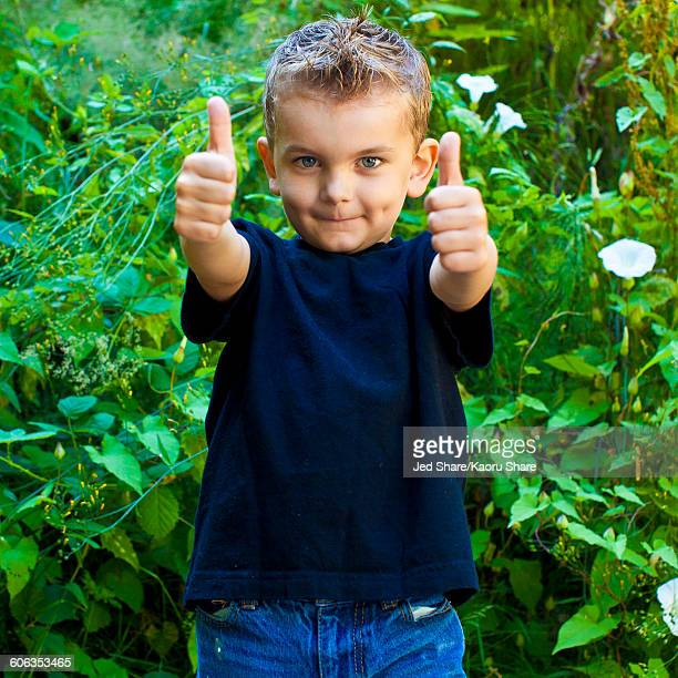 Caucasian boy giving thumbs up in garden
