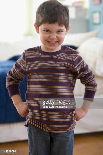 Caucasian boy grimacing with hands on hips