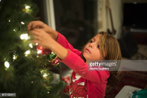 Caucasian boy hanging ornament on Christmas tree