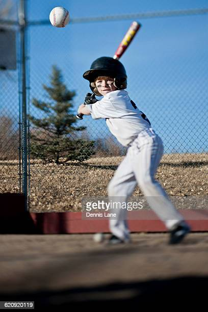 caucasian boy hitting baseball on field - eye black stock photos and pictures