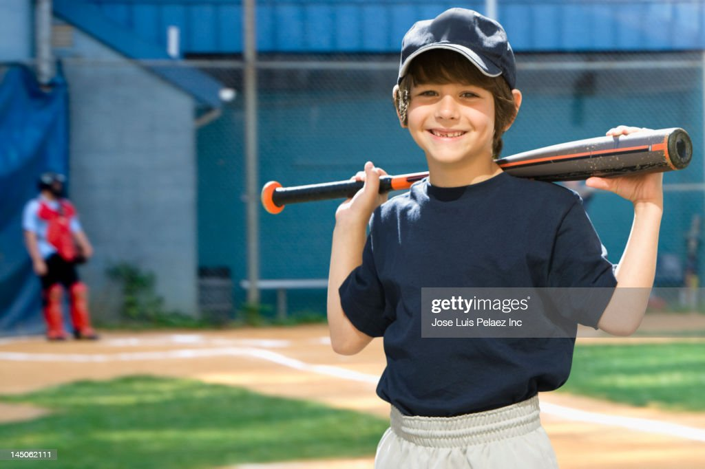 Caucasian boy holding baseball bat on field : Stock Photo