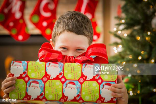 Caucasian boy holding Christmas gift