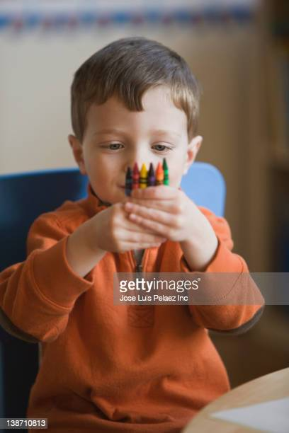 Caucasian boy holding crayons