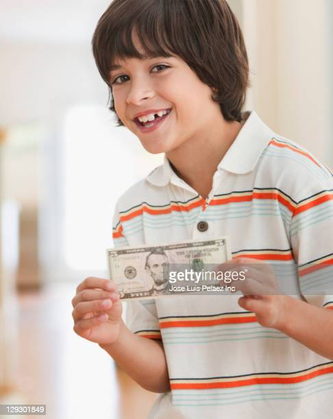 Caucasian boy holding five dollar bill