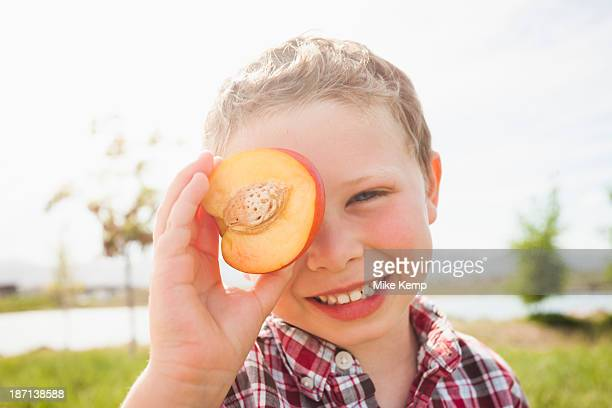 Caucasian boy holding fruit over eyes